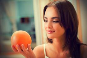 Beautiful-brunette-looking-at-Grapefruit